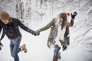 Happy couple running in winter forest - SUF00429