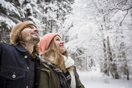 Smiling couple in winter forest watching snow fall - SUF00435
