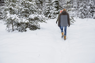 Couple walking in winter forest - SUF00438