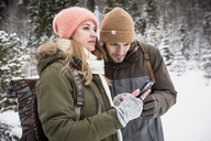 Couple on a trip in winter using cell phone - SUF00441