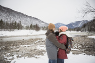 Happy couple hugging on a trip in winter - SUF00444