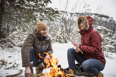 Happy couple on a trip in winter having a break at camp fire - SUF00447