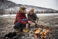 Couple on a trip in winter warming hands at camp fire - SUF00450