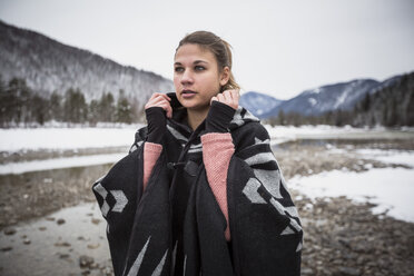 Young woman standing at a river in winter - SUF00456