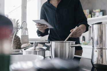Man standing in kitchen reading news on his digital tablet while cooking - KNSF03424