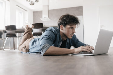 Man lying on the floor in a loft using laptop - KNSF03430