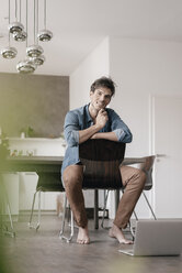 Portrait of smiling young man sitting on chair in a loft - KNSF03439