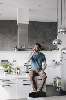Man sitting on kitchen counter eating an apple - KNSF03442