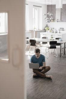 Man sitting on the floor in the kitchen working on laptop - KNSF03448