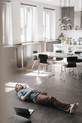 Man lying on the floor in a loft having a rest - KNSF03451