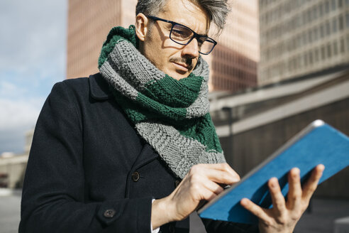 Portrait of businessman using tablet outdoors - JRFF01497