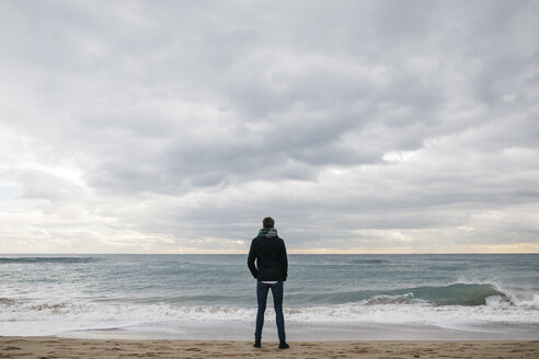 Back view of man standing on the beach in winter looking at distance - JRFF01506