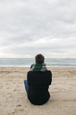 Back view of man sitting on the beach in winter looking at distance - JRFF01509