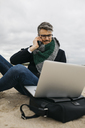 Portrait of businessman on the phone sitting on the beach in winter using laptop - JRFF01512