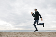 Man jumping on the beach in winter - JRFF01515