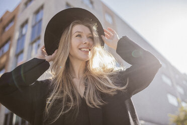 Portrait of happy woman with hat dressed in black - KMKF00135
