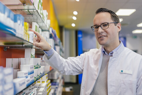 Portrait of smiling pharmacist with medicine at shelf in pharmacy - MFF04285