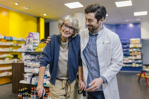 Portrait of smiling pharmacist and customer with wheeled walker in pharmacy - MFF04288