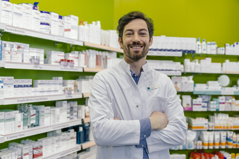 Portrait of smiling pharmacist at shelf with medicine in pharmacy - MFF04291