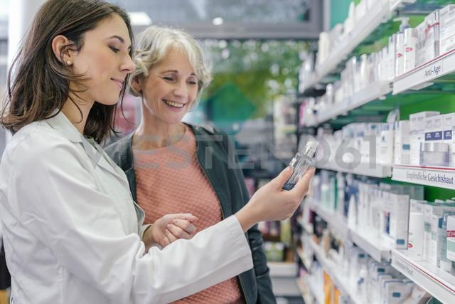 Pharmacist advising customer with cosmetics in pharmacy - MFF04297