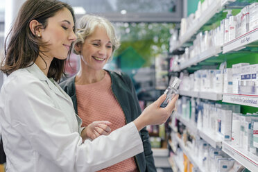Pharmacist advising customer with cosmetics in pharmacy - MFF04297