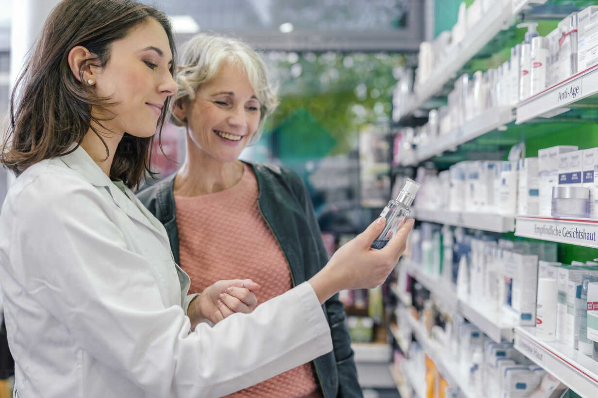 Pharmacist advising customer with cosmetics in pharmacy - MFF04297 - Mareen Fischinger/Westend61