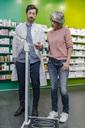 Pharmacist advising customer with sclaes in pharmacy - MFF04303