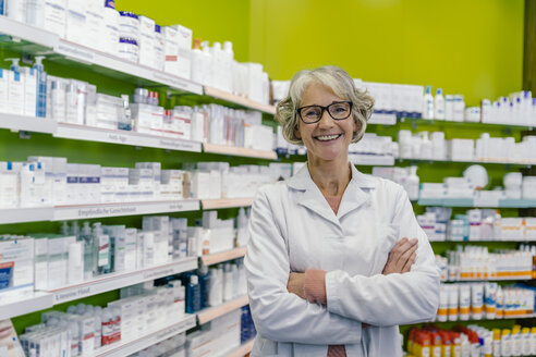 Portrait of smiling pharmacist at shelf with medicine in pharmacy - MFF04306