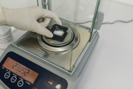 Hand with protective glove using scales in laboratory of a pharmacy - MFF04315
