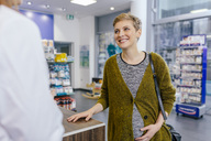 Pharmacist advising pregnant woman in pharmacy - MFF04318