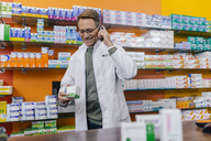 Smiling pharmacist talking on phone at counter in pharmacy - MFF04321