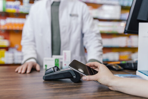 Close-up of customer paying cashless with smartphone in a pharmacy - MFF04324