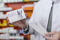 Pharmacist holding tablet package and prescription in pharmacy - MFF04333