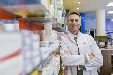 Portrait of smiling pharmacist leaning against shelf with medicine in pharmacy - MFF04336