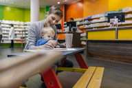 Little boy with mother sitting on bench in pharmacy - MFF04339