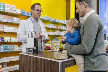 Pharmacist advising father with son in pharmacy - MFF04342