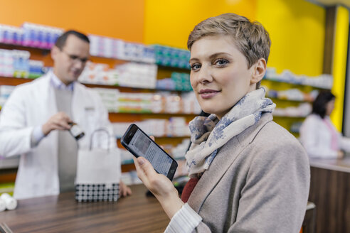 Portrait of woman with cell phone at counter in pharmacy - MFF04345