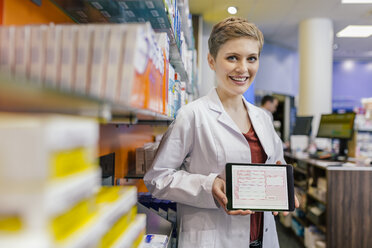 Portrait of smiling pharmacist in pharmacy holding tablet with digital prescription - MFF04348
