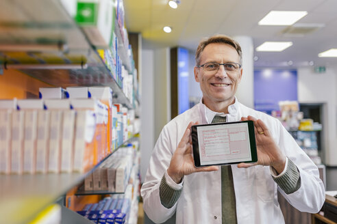 Portrait of smiling pharmacist in pharmacy holding tablet with digital prescription - MFF04351