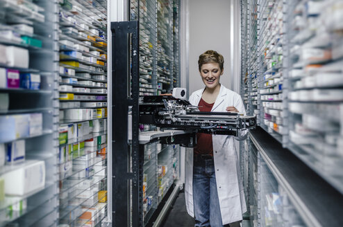 Smiling pharmacist with commissioning machine in pharmacy - MFF04357