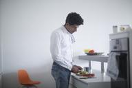 Man standing in kitchen preparing vegetables - SGF02140