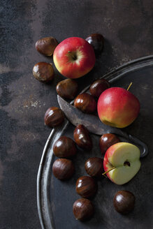 Sliced and whole apples, sweet chestnuts and an old knife on rusty background - CSF28686