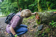 Costa Rica, Woman looking at a mushroom on a tree trunk - KIJF01848