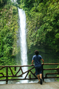 Costa Rica, Arenal Volcano National Park, Man looking at  the waterfall of La Fortuna - KIJF01854