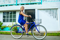 Panama, Bocas del Toro, Woman riding a bicycle, looking at camera - KIJF01866