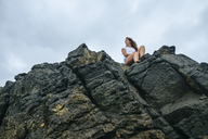 Costa Rica, Woman sitting on rocks, view from below - KIJF01884