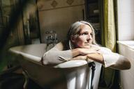 Portrait of sad woman sitting dressed in bathtub - KNSF03459