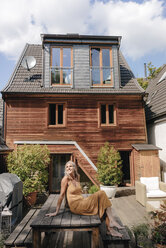 Happy woman sitting on terrace of her house - KNSF03462