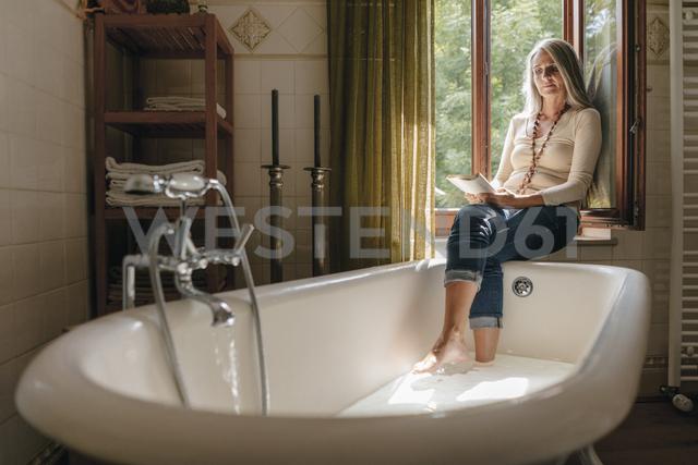 Woman sitting on window sill in the bathroom taking footbath while reading a book - KNSF03465 - Kniel Synnatzschke/Westend61