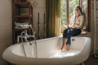 Woman sitting on window sill in the bathroom taking footbath while reading a book - KNSF03465